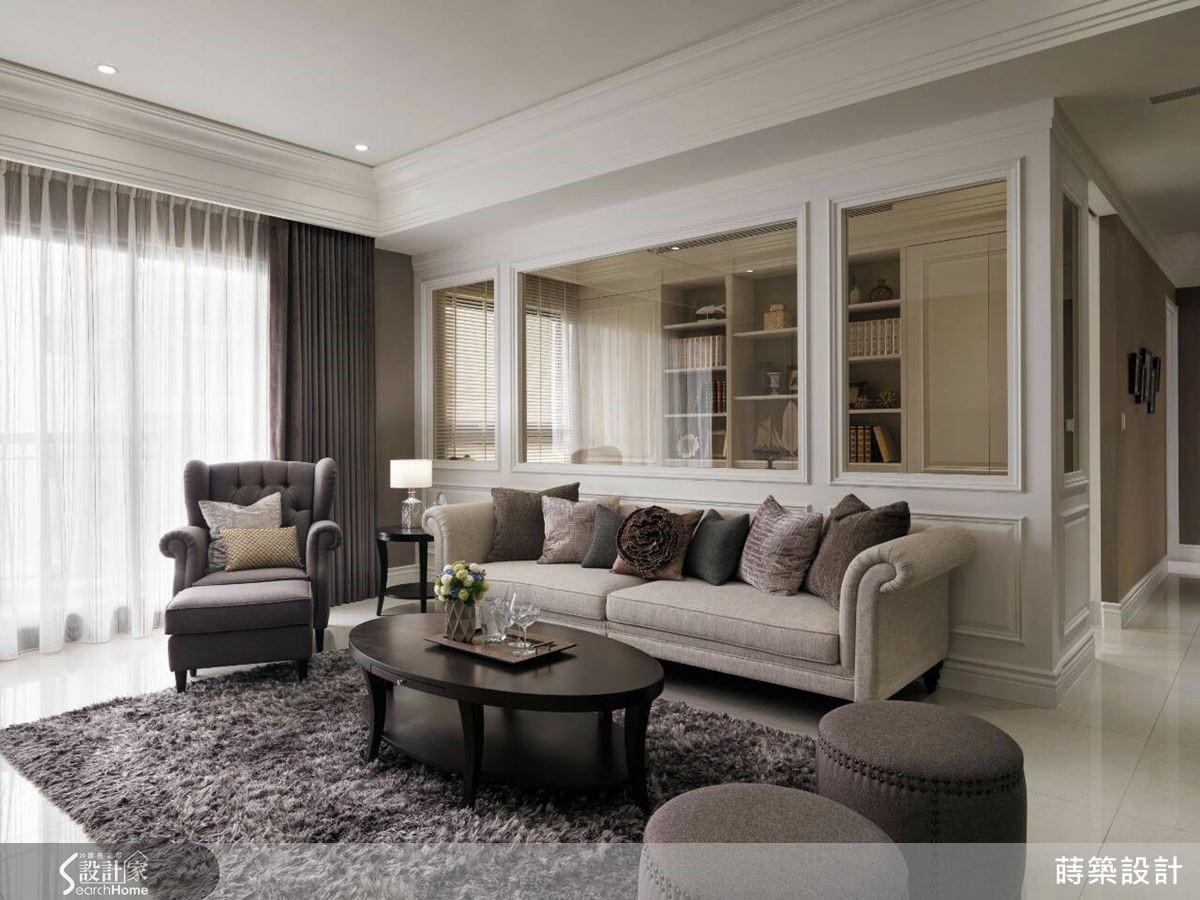 客廳沙發背牆以左右對稱的優雅比例線板,搭配清玻璃的虛實輕重來延展視覺穿透性,清楚界定空間場域,以其強調新古典的簡約與和諧秩序之美。