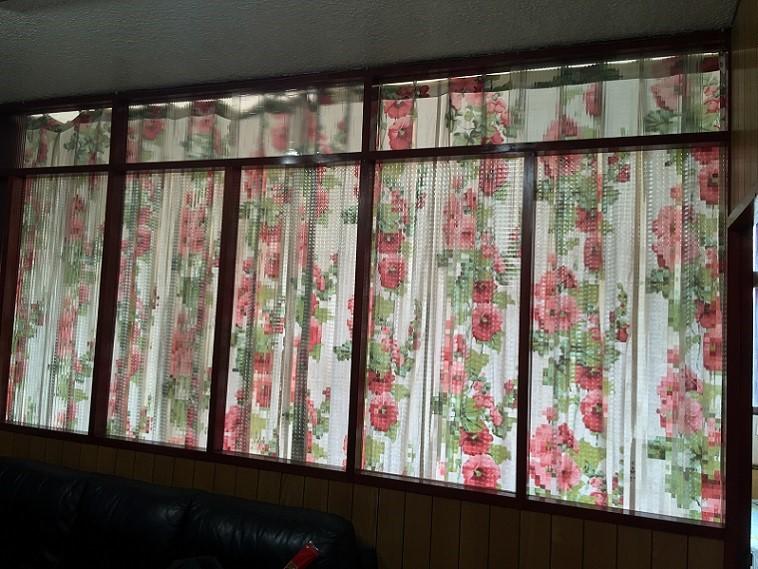 有嚴重西曬的長輩房,利用檜木玻璃隔間與簾幕為客廳作為遮擋陽光的工具,卻使客廳長年累月的壟罩在陰暗之中。