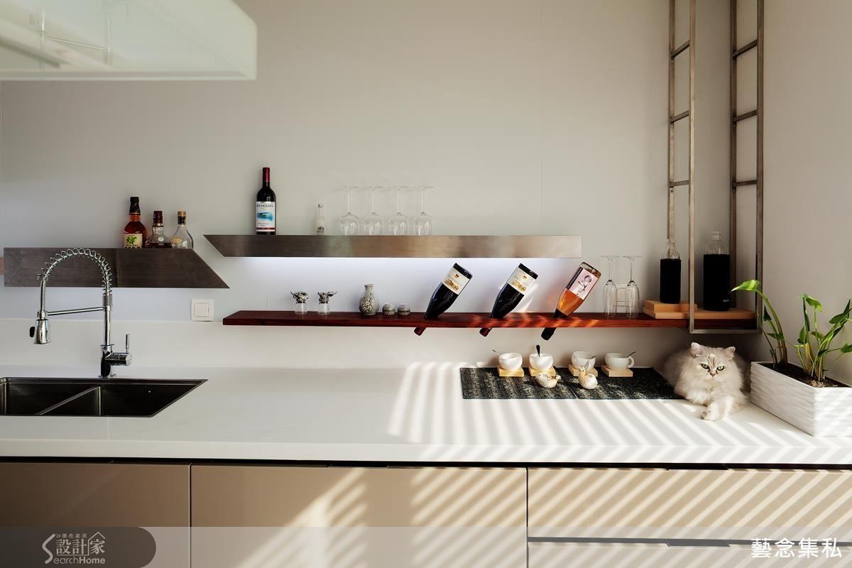 流理檯上方捨棄一般的廚具上櫃,以台灣鐵工優異技術融合酒吧式概念,打造紅酒、酒杯置放空間,讓廚房主牆有了陳列美感,營造現代時尚氛圍。